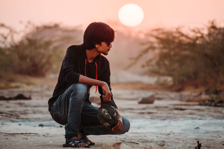 Full length of man wearing sunglasses crouching on field against sky during sunset