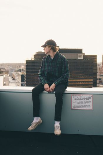 Teenage Boy Sitting On Retaining Wall Against Clear Sky