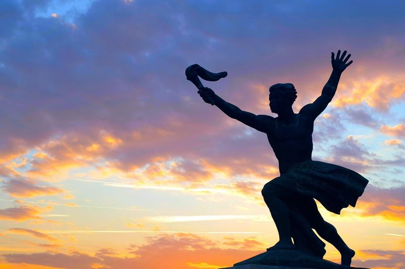 Low Angle View Of Silhouette Statue Against Cloudy Sky During Sunset