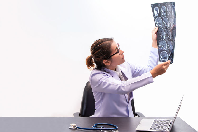 Diagnosis Adult Communication Computer Doctor  Female Doctor Females Healthcare And Medicine Healthcare Worker Holding Indoors  Laptop Looking Medical Exam Medical X-ray Occupation One Person Professional Occupation Sky Technology Using Laptop Waist Up Wireless Technology Women