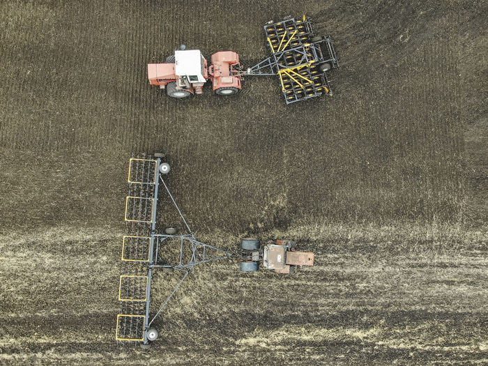 Aerial view of a modern tractor plowing dry field, preparing land for sowing Aerial Agriculture Field Tractor Farm Ground Soil Countryside Combine Machinery Motion Working Plowing High Angle View Technology Directly Above Environment Transportation Land
