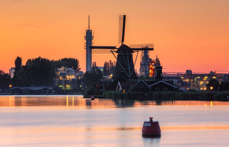 Industry and traditional windmill near the zaanse schans at sunset