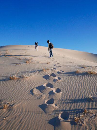 People on sandy desert against clear blue sky