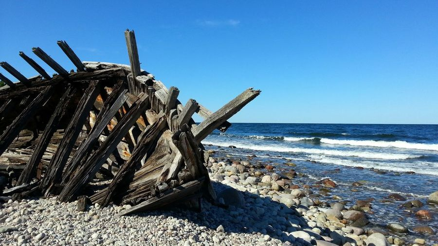 Abandoned Shipwreck On Beach Against Clear Blue Sky