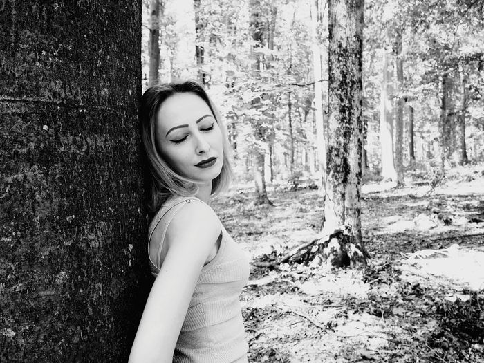 Woman With Closed Eyes Standing Against Tree At Forest