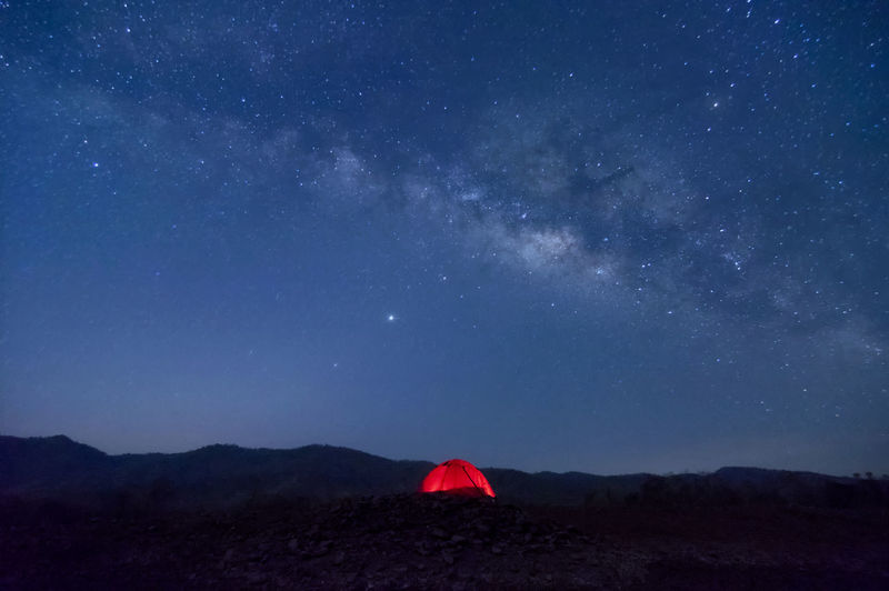Red tent in reservoir under milky way galaxy with starsbaan sop pat, mae moh lampang thailand.