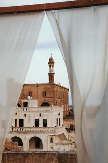Historic building seen through curtain against sky