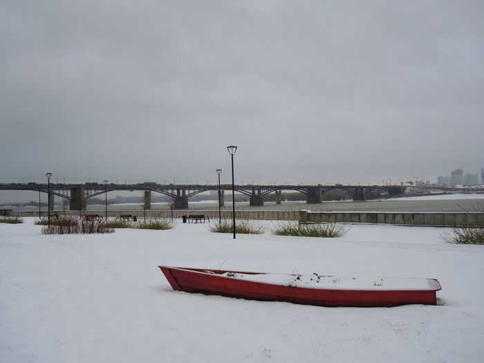Boat moored on snow covered shore against sky