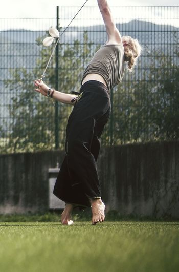 Woman Juggling On Grassy Field Against Fence