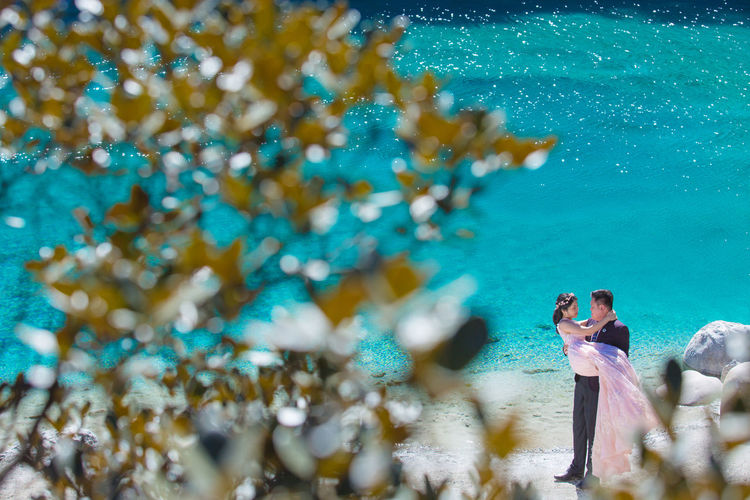 High Angle View Of Newlywed Couple Romancing At Beach