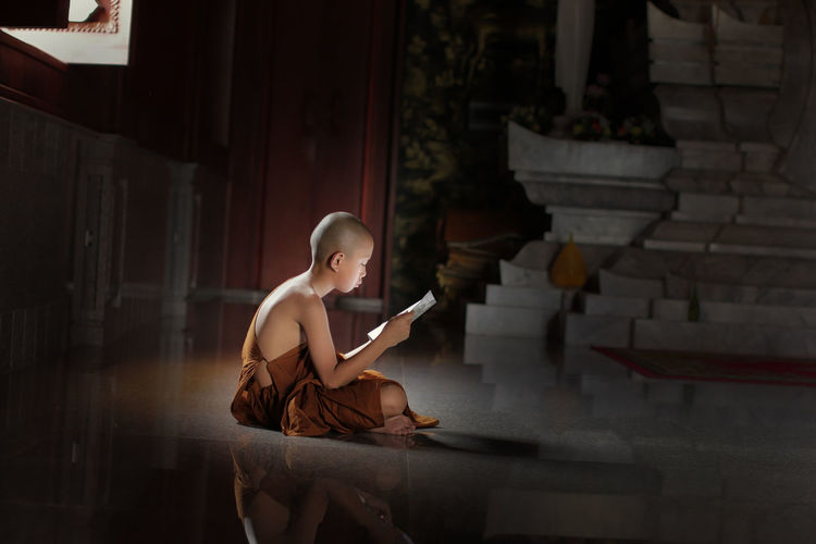 Novice monk learning in Temple, Thailand. Book Day Full Length Indoors  One Person People Real People Sitting Wireless Technology Young Adult