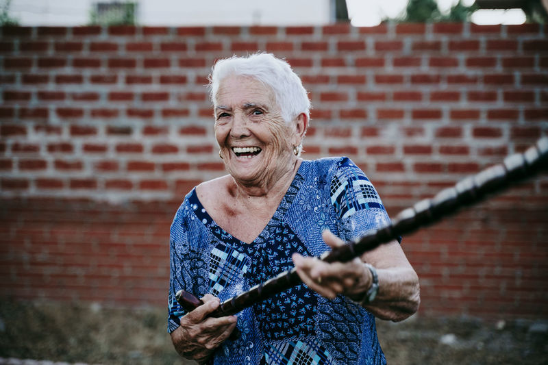 Portrait of smiling senior woman holding cane standing outdoors