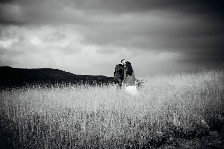 Rear View Of Couple Kissing While Standing On Grassy Field Against Cloudy Sky