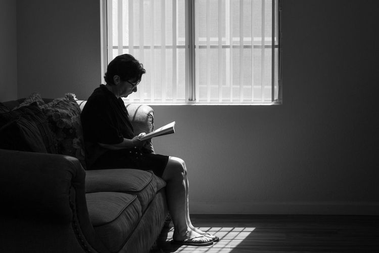 Silhouette Mature Woman Reading Book While Sitting On Sofa At Home