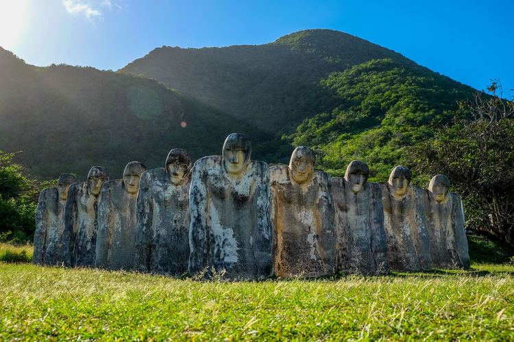 Large old statues on grass against mountains