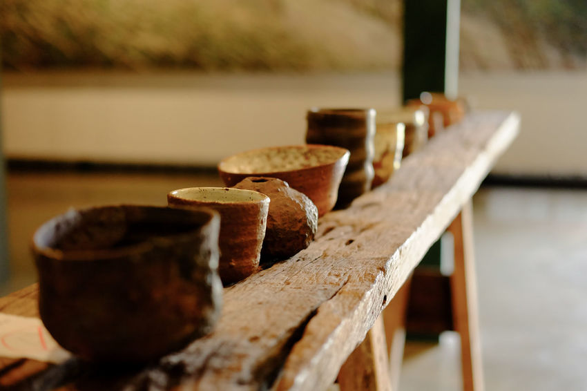 Art and craft Art And Craft Container Pottery Cup Bench Bowl Brown Celadon Craft Cup Earthenware Exhibition Focus On Foreground In A Row Museum Nature Old Rusty Seat Selective Focus Seramic Soil Table Wood - Material
