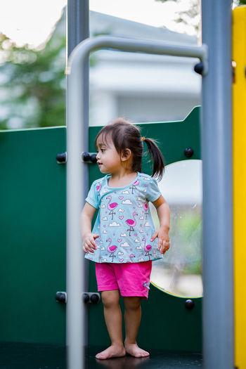 Full length of girl standing on play equipment