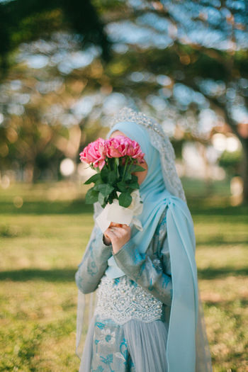 Bride covering face with bouquet while standing at park