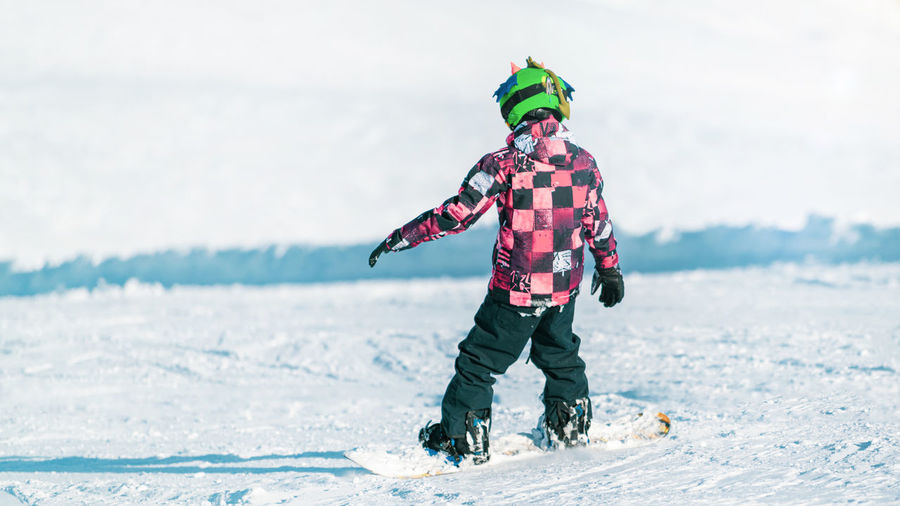 Child snowboarding in the mountains