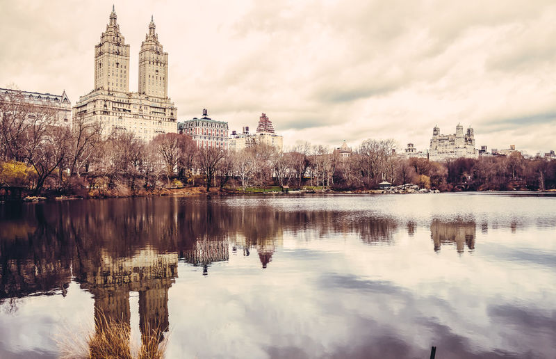 Reflection of the san remo on central park reservoir against cloudy sky