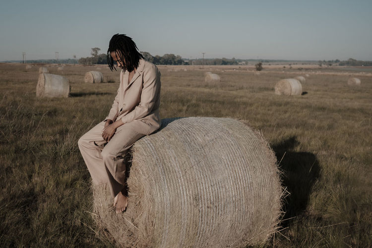 Full length of young man sitting on hay bale at agricultural landscape