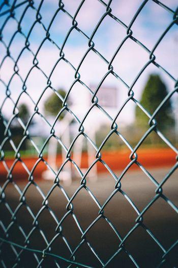 Full frame shot of soccer field seen through chainlink fence