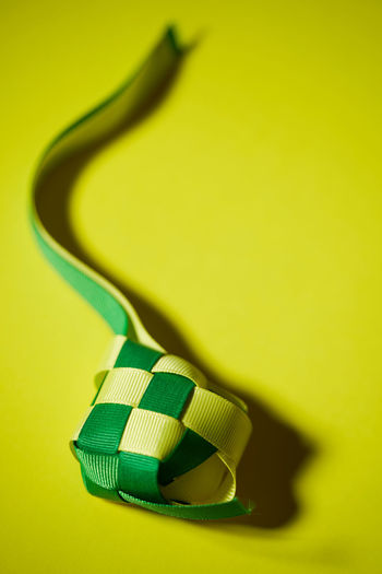 Close-up of yellow object over green background