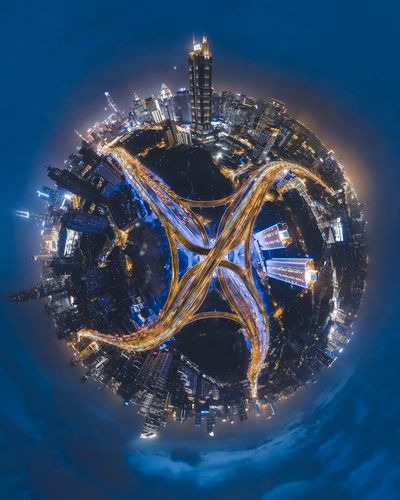 Little planet format of illuminated buildings against sky