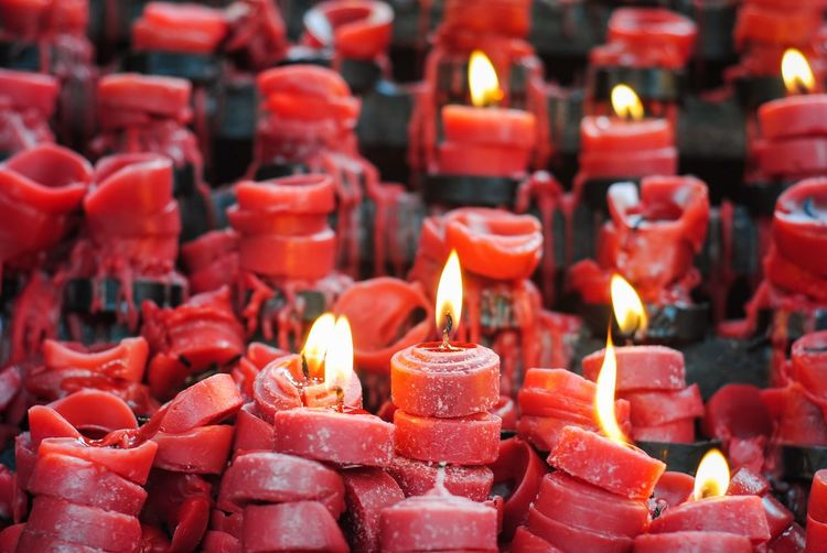 Full Frame Shot Of Lit Candles In Temple