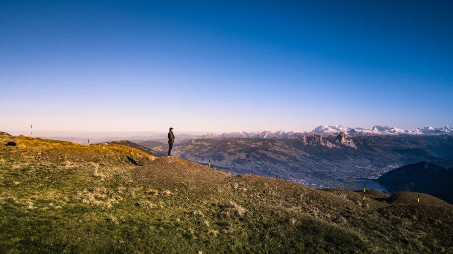 Man standing on landscape against blue sky
