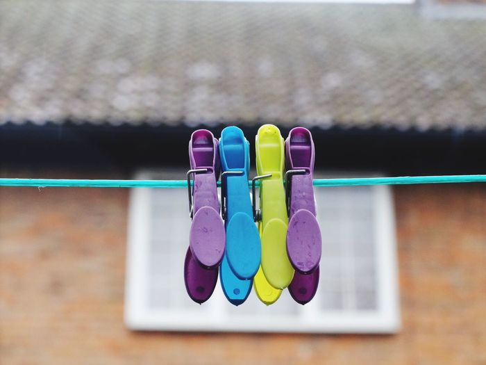 Close-Up Of Colorful Clothespins Hanging From String Outside House