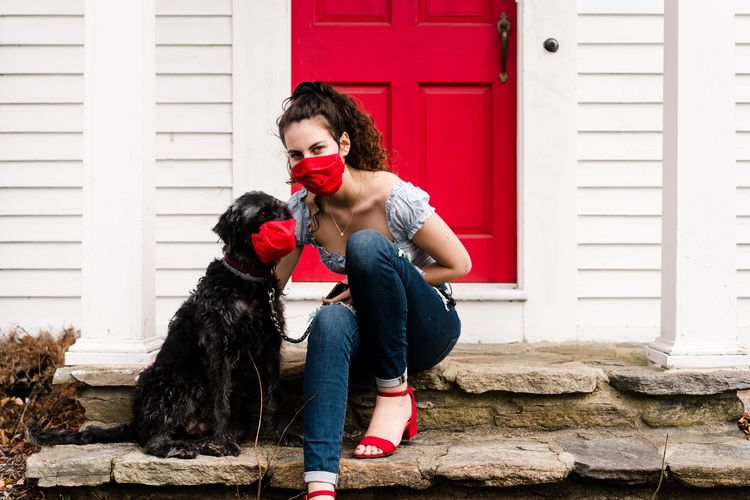 Woman with dog against built structure