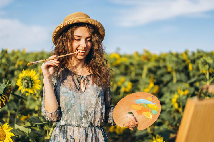 Woman wearing hat holding plants against sky
