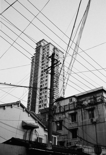 Cable Architecture Built Structure Building Exterior Electricity  Power Line  Low Angle View Sky Building Technology No People Power Supply Electricity Pylon Connection Nature Fuel And Power Generation Day Residential District City Complexity Outdoors Electrical Equipment Telephone Line Blackandwhite