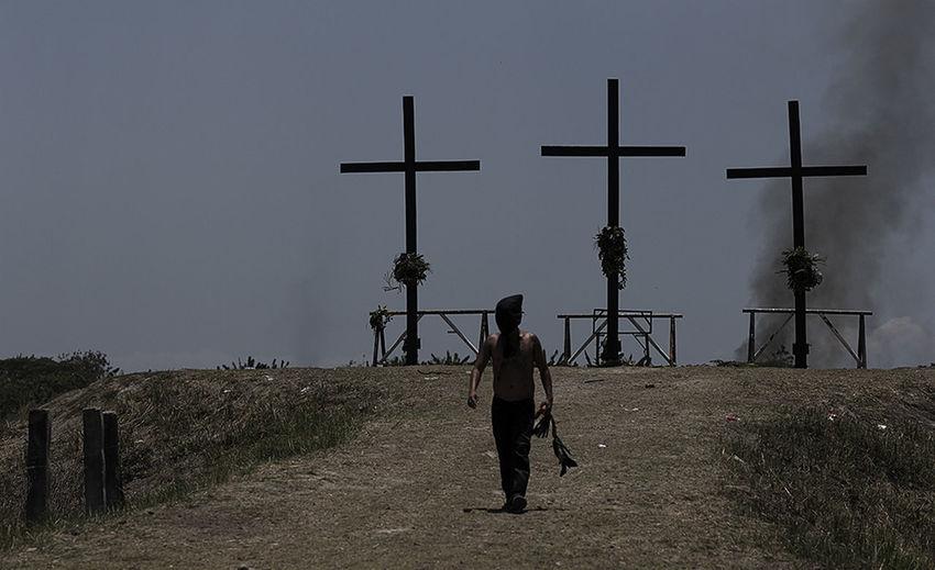 Full length of man on cross against sky