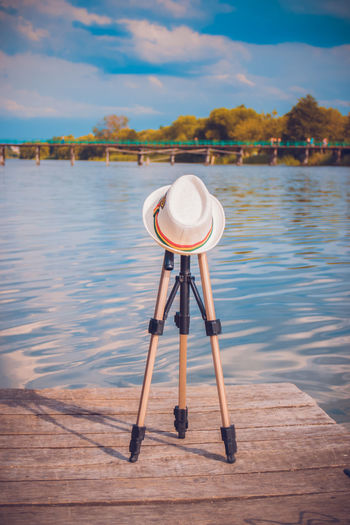 A tripod covered with a hat on the wooden pier of the pier. concept of rest.