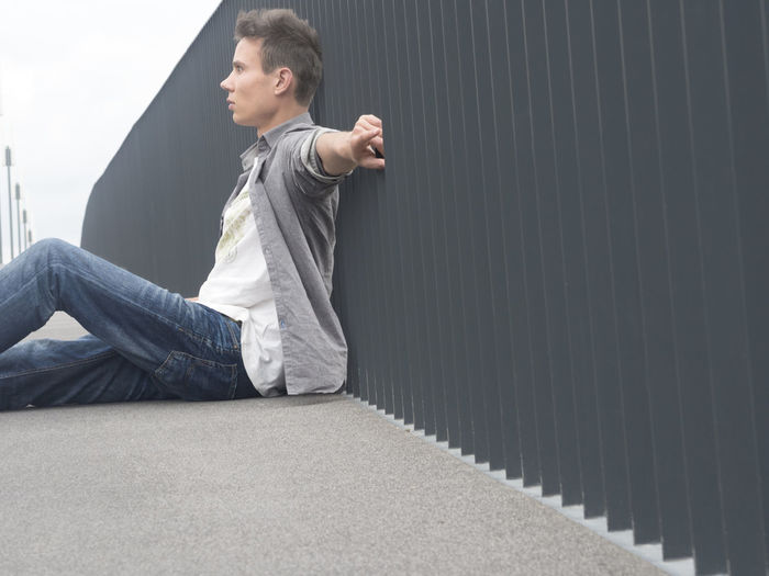 Side View Of Young Man Sitting By Railing On Footpath
