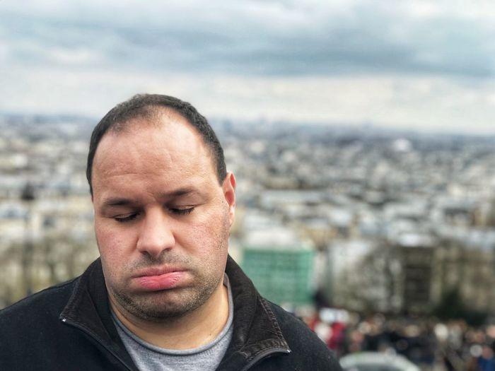 Close-up of tired man standing against cityscape