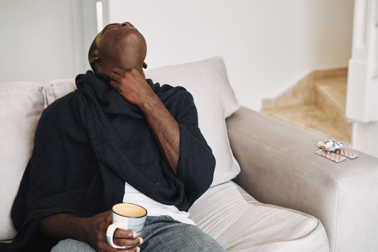 Man holding coffee cup sitting on sofa at home