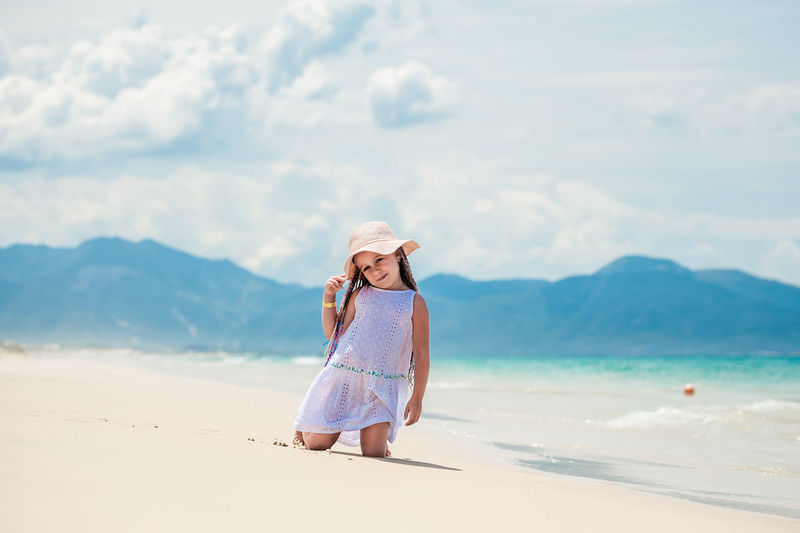 Cute girl kneeling on beach against sky