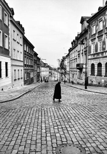 Senior woman walking on street amidst buildings against sky