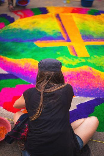 Rear view of woman making colorful rangoli