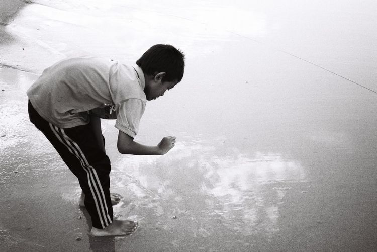 Side view of boy standing in water