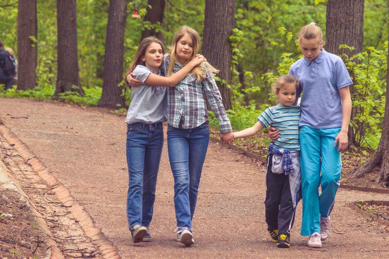 Full length of sisters walking on road