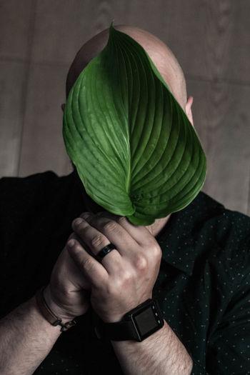Close-up of man holding leaf
