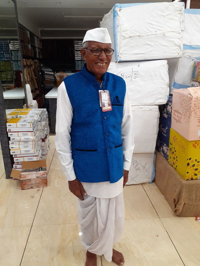 Portrait of smiling senior man against boxes in warehouse
