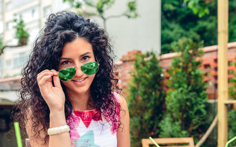 Portrait of smiling young woman with curly hair looking at camera over blue sunglasses outdoors Cocktail Fiends Happiness Happy Horizontal Looking At Camera Young Caucasian Cheerful Curly Hair Drink Enjoy Friendship Leisure Lifestyles One Person Outdoors Party People Portrait Real People Smiling Summer Sunglasses Togheter