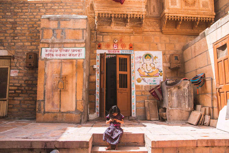 golden streets of Jaisalmer .. Architecture Built Structure Art And Craft Text Day Building Exterior Religion One Person Human Representation Creativity Belief Representation Spirituality Sitting Building Real People Place Of Worship Entrance History Outdoors Girl Rajasthan Sandstone Jaisalmer Storytelling Streetphotography Street Cultures India Door The Photojournalist - 2019 EyeEm Awards The Traveler - 2019 EyeEm Awards The Street Photographer - 2019 EyeEm Awards