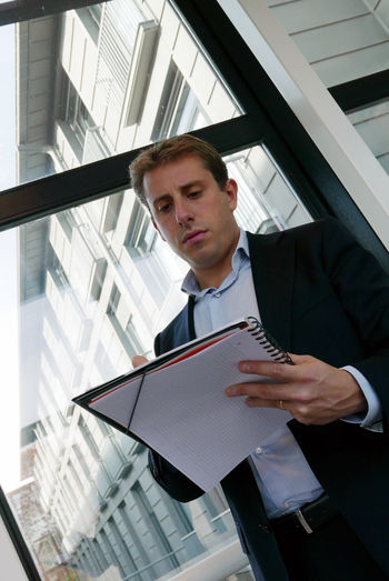 Businessman Standing With Documents Against Window At Office Corridor
