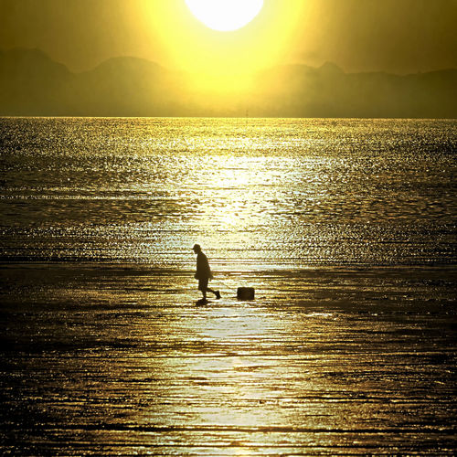 Beauty In Nature Gold Colored Horizon Over Water Idyllic Mountain Nature One Person Outdoors Real People Reflection Rippled Scenics Sea Silhouette Sky Sun Sunlight Sunset Tranquil Scene Tranquility Vacations Water Waterfront